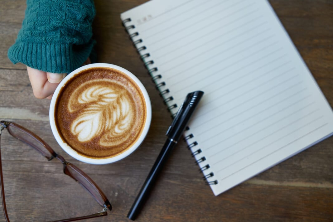 A cup of coffee, notebook, and pen. For an article about becoming a freelance writer