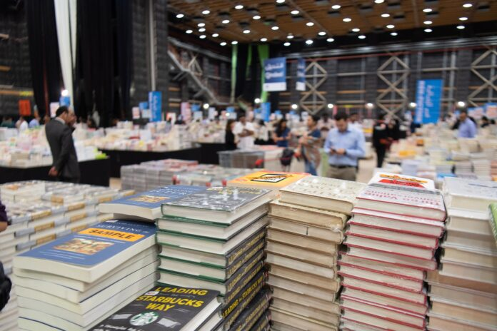 Pile of books at a book fair. For a post about literary vs commercial fiction