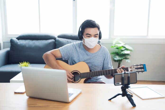 An Asian man wearing a face mask and playing a guitar into a laptop during lockdown