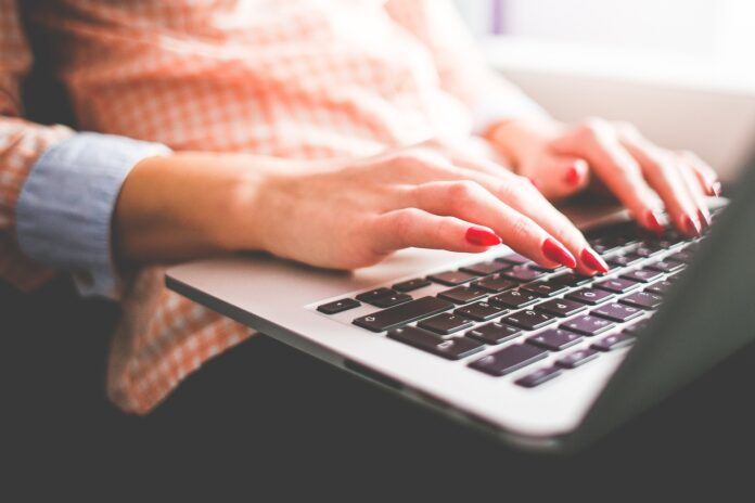 Woman typing on a laptop, for a post about first-person writing ideas
